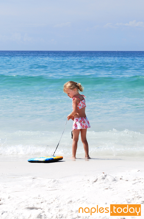 Girl on Naples beach with boogie board