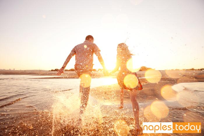 Happy couple running on Naples beach