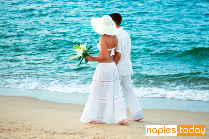 Romantic couple walking along Naples beach