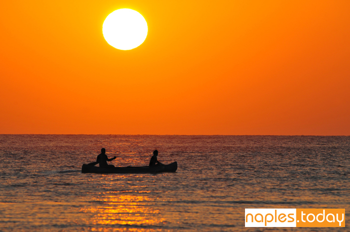 Silhouette of a two men on a boat at sunset
