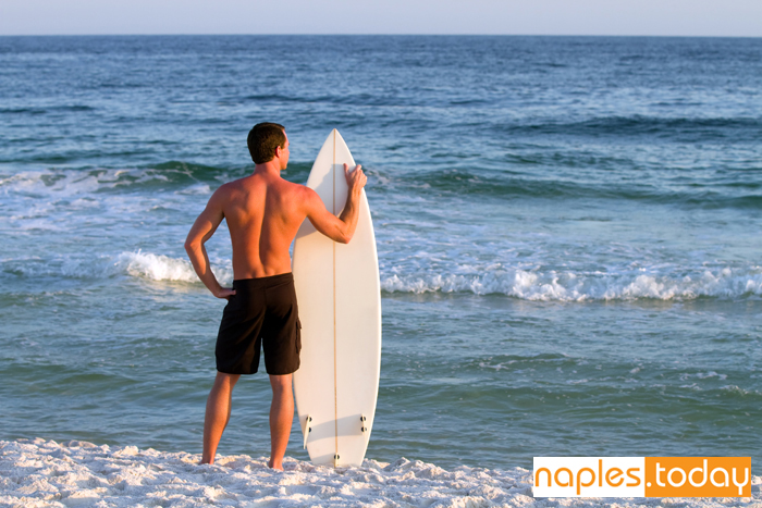 Surfer stands by the shoreline holding his board