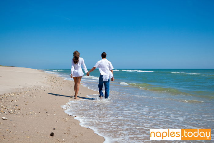 Young couple walking on Naples beach