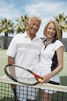Active senior couple on the tennis court