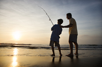 Father and son fishing in ocean surf at sunset