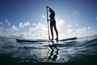 Young female paddles a paddleboard off Naples beach